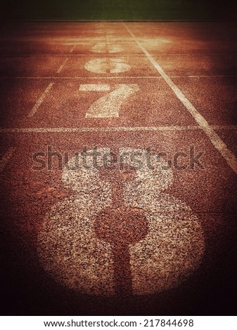 Running track racing texture with number , dark feeling, retro filter effect  - stock photo