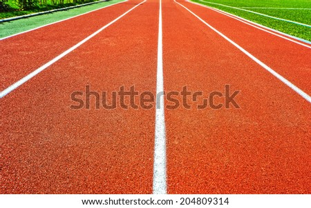 Running Track . Red treadmill at the stadium with white lines . - stock photo