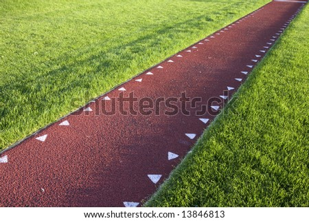 running track with a red synthetic surface for a long jump competition - stock photo