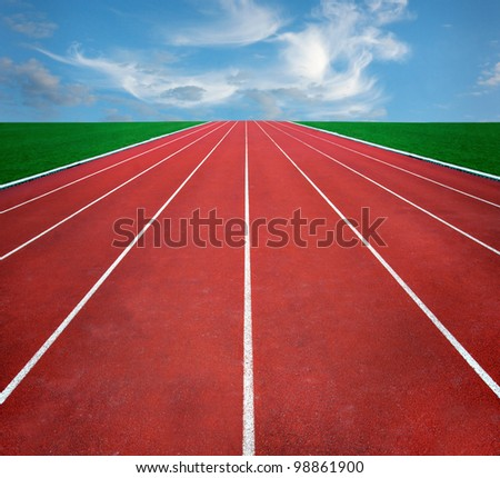 Running track with blue cloudy sky in distance - stock photo
