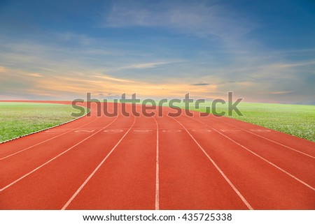 Running track with green grass and blue sky white cloud background - stock photo
