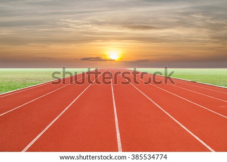Running track with green grass and  sky sunset - stock photo