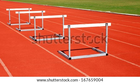 running tracks with three hurdles set up for training - stock photo
