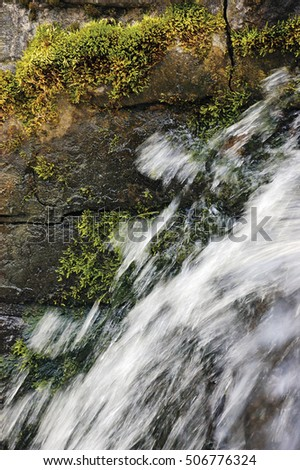 Running water cascade waterfall streaming splashes, decorative granite stonewall background, green moss, grey rock stone wall vertical masonry closeup bright white motion blurred drops texture pattern