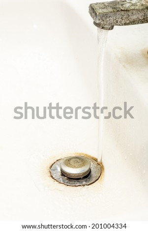 running water on drain stopper plug of washbasin - stock photo