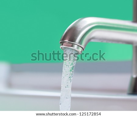 Running water out of modern faucet - stock photo