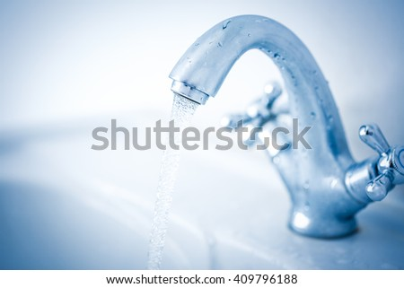 Running water tap closeup in toning clean - stock photo