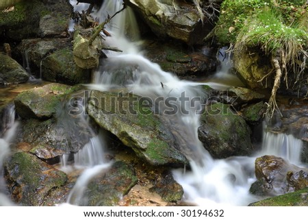 Running waterfall in forest - stock photo