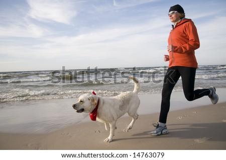 Running with dog on the beach - stock photo