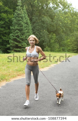 Running with dog. Woman is jogging with dog Jack Russell terrier in park