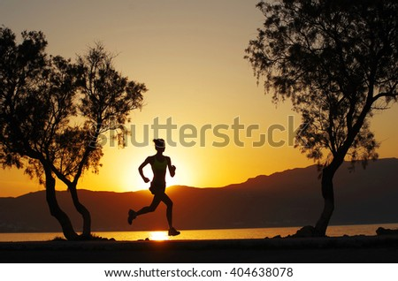 Running woman athlete silhouette on a boulevard at sunset, with a warm full sun and a little fog - stock photo