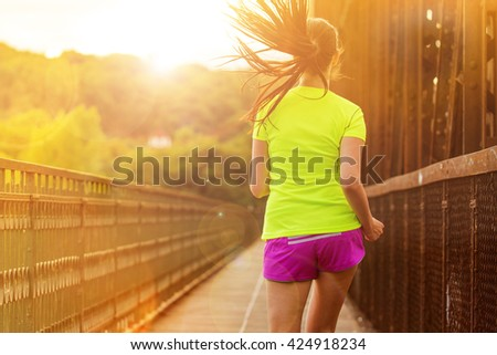 Running woman during sunny day in the city. Female fitness model training outside in Prague. - stock photo