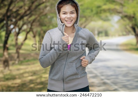 Running woman. Female runner jogging during outdoor on road .Young mixed race girl jogging in fall colors. - stock photo