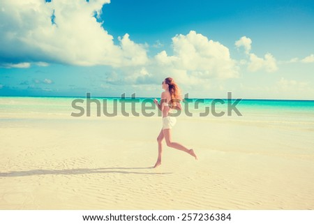 Running woman. Female runner jogging during outdoor workout on beach. Beautiful fit girl Fitness model outdoors. - stock photo