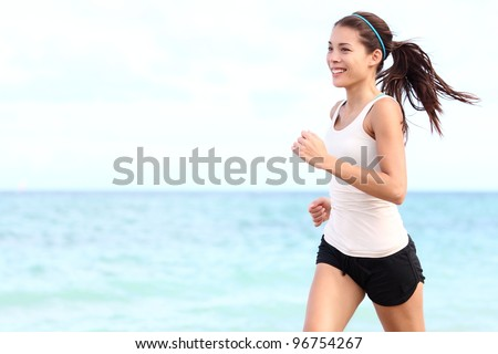 Running woman. Female runner jogging during outdoor workout on beach. Beautiful fit mixed race Fitness model outdoors.