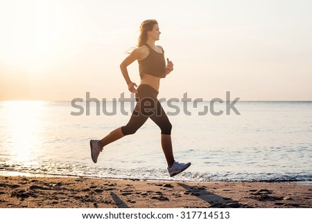 Running woman. Female runner jogging during the sunrise on beach.