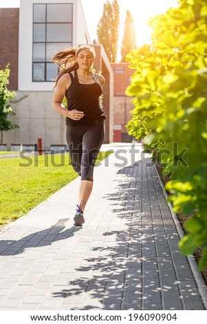Running woman in black sport outfit on the sidewalk  - stock photo