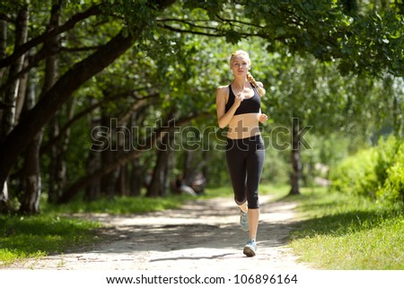 Running woman in park in summer training. - stock photo