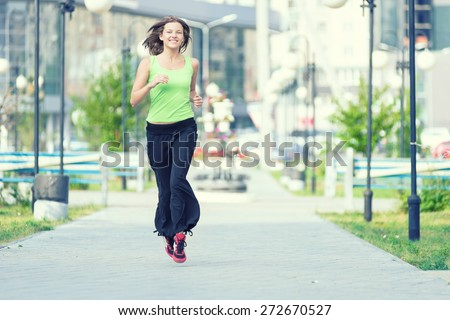 Running woman jogging in city street park at beautiful summer morning. Sport fitness model caucasian ethnicity training outdoor.