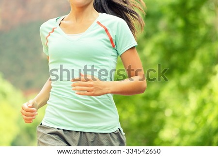 Running Woman Jogging. Midsection of determined woman runneron sunny day. Young female is in sports clothing. Sporty athlete runner is exercising against trees. - stock photo