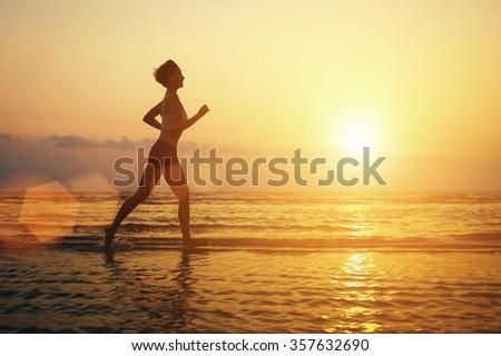 Running woman on the beach sport silhouette. Sunrise, sun reflection on sea water. Freedom, beauty - stock photo