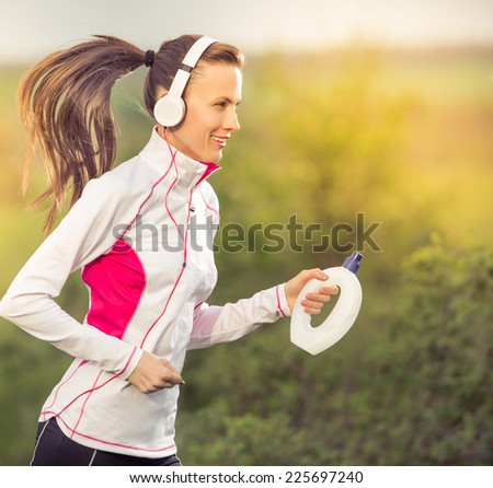 Running woman. Runner is jogging in sunny bright light in the autumn park background. Female fitness model training outside on a warm fall day and listening to music in motion. Sport lifestyle - stock photo