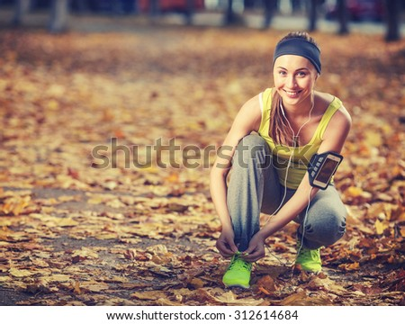Running woman. Runner is tying laces and listening to music. Female fitness model tying laces outside in autumn park. Woman athlete training in the fall outdoors background. Sport lifestyle. - stock photo