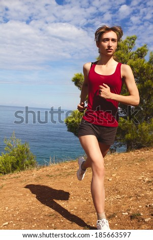 Running woman. Runner jogging in sunny bright light. Summer sea. Female fitness model training. Female runner jogging during outdoor workout on beach.
