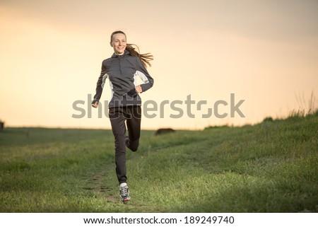 Running woman. Runner jogging over sunset sky. Female fitness model training outside in motion focus on face - stock photo