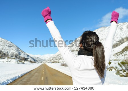 Running woman success sport concept on winter road mountain background. Sportswoman winning on snowy landscape. - stock photo