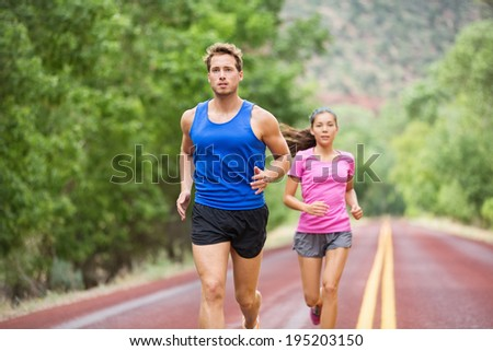Running young fitness couple training marathon concentrated focused on road trail in summer nature. Sporty healthy mixed race woman and handsome caucasian man jogging outside. Athletic people in 20s - stock photo