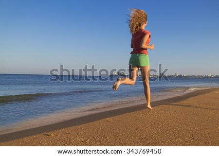 Running young woman. Female runner jogging during outdoor workout on beach. - stock photo