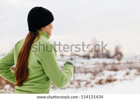 Running. Young  woman jogging in snow. Health and fitness concept