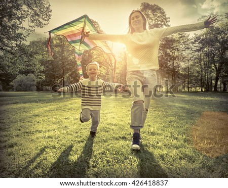 Runnings little boy and mother flies with them kite in the park under sunligt.