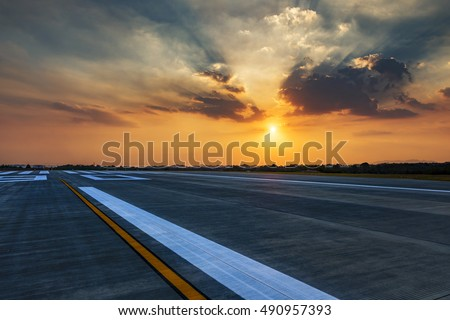 Runway, airstrip in the airport terminal with marking in sunset background. Travel aviation concept.