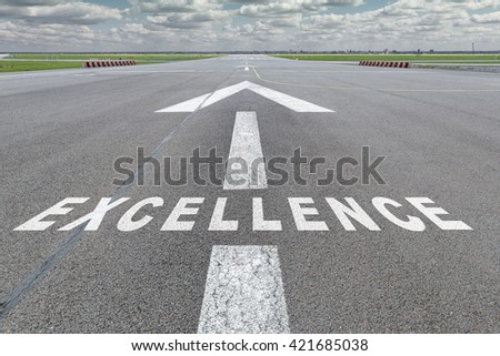 Runway of airport with arrow guideline and Excellence letters painted on the surface - stock photo