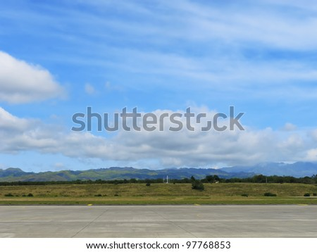 Runway of small airport shot against a backdrop of mountains and blue sky