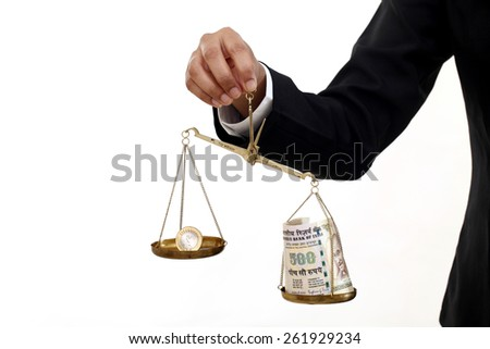 Rupee coin and Indian currency notes in justice scale - stock photo