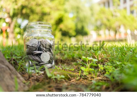 Rupiah Coin Money in jar on Green Grass Nature Background