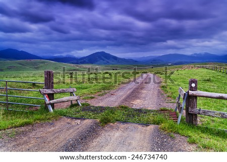 Rural agricultural property dividing fence, grid and gate on unsealed road through property in stormy valley with green grazing grass surrounded by hilly mountains - stock photo