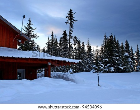 Rural Alaskan house buried in snow with a snow shovel and spruce trees in the background.