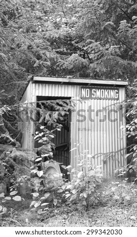 Rural Alaskan shed with 'no smoking' sign in black and white. - stock photo