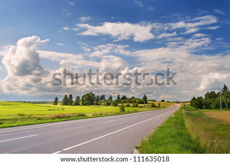Rural asphalt road on sunny summer day - stock photo