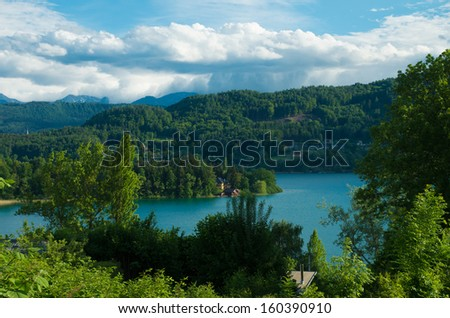 rural austrian landscape with a view over the worther see in carinthia - stock photo