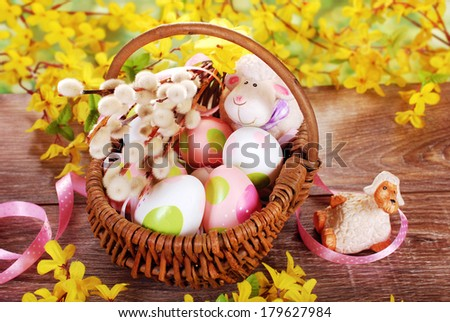 rural braided basket with painted eggs and funny sheep figurine on wooden table for easter - stock photo