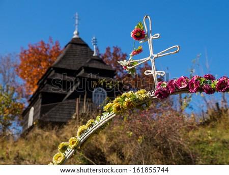 Rural church gate decorated with artificial flowers - St. Michael church in Uzhok, Zakarpattia Oblast, Ukraine (built circa 1740, UNESCO World Heritage Site since 2013) - stock photo
