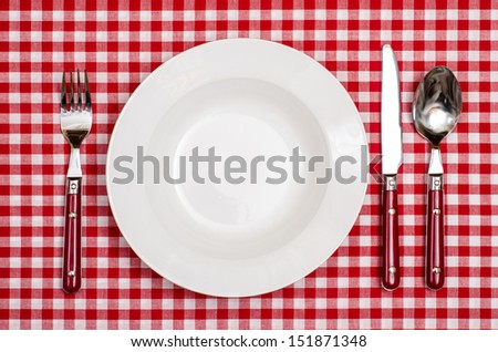 Rural cover with plate, fork, knife an spoon on a table with red checkered cloth