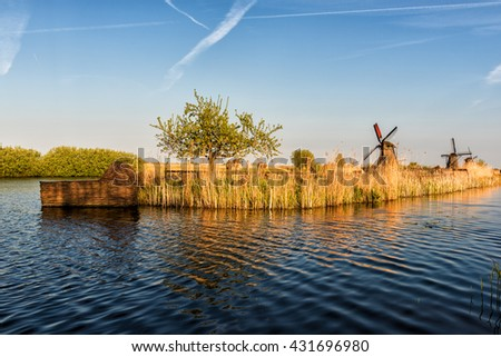 Rural dutch landscape with windmills, water and grass at soft sunset light, Kinderdijk, Netherlands - stock photo