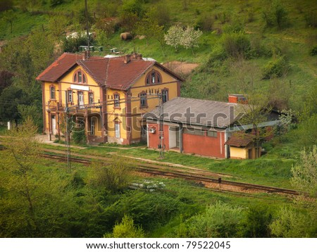 rural european vintage yellow train station in green nature surrounding - stock photo