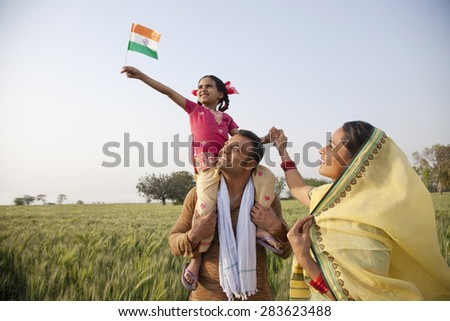 Rural family in the field with girl holding Indian flag - stock photo